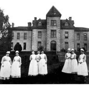 Nurses standing by the old hospital